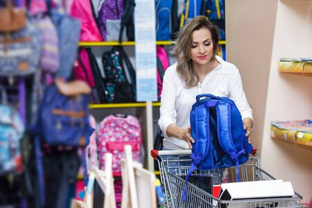 Mother buying school bag in mall. A young woman with a troley is shopping at a supermarket. 版權商用圖片