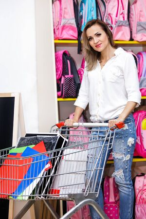 Woman hold a trolley in a supermarket with purchases. Lady in a white blouse on the background of school backpacks makes a shopping.