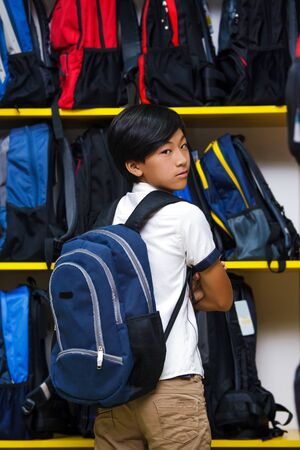 Asian boy chooses schoolbag in the submarket. Portrait of a schoolboy in the background of backpacks.