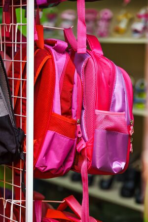 Many pink backpacks on the shelf in the supermarket.