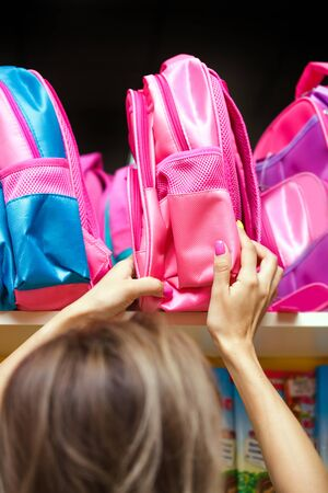 Mother chooses a pink school backpack for her daughter. Female hands hold a bag in a supermarket.