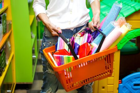 Female hands hold a orange shopping basket in a supermarket with purchases.