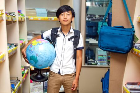 Asian boy chooses stationery in the submarket. The schoolboy holding a globe and buying.