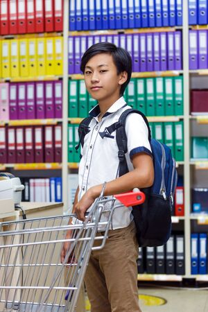 Asian boy chooses stationery in the submarket. The schoolboy holding a trolley. 版權商用圖片