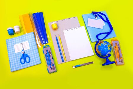 School things, notebook and stationery of blue color over yellow desk. Back to school abstract background.