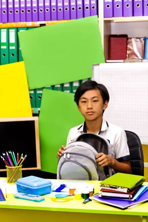 A classman studies in the classroom or library and does homework. Portrait of a schoolboy sitting at table with books.
