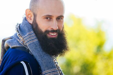 Bald man with a beard and scarf smiling on the nature and sky background.