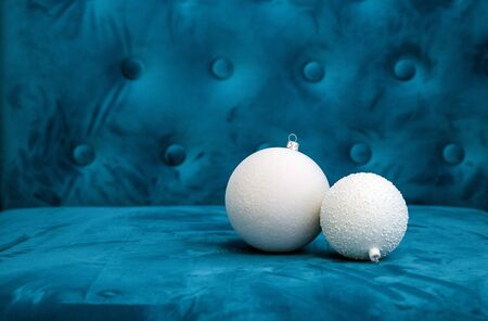 Two white New Year's toys are on a blue sofa.  sofa with Christmas toys Banco de Imagens