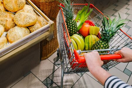Woman in the supermarket with basket buy fruits and vegetables. Fitness lady in street market control calories and makes choice for healthy foods. Stok Fotoğraf