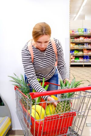 Woman in the supermarket with basket buy fruits and vegetables. Fitness lady in street market control calories and makes choice for healthy foods.