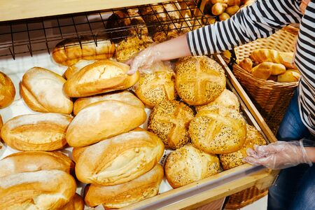 Female hands takes bread from shalves in the bakery. Fresh different rolls in supermarket or batch. Imagens