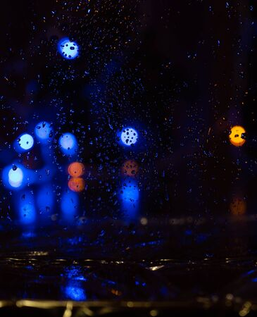 Rain drops on window with bokeh on blure background. Night on the street and a lot of multicolored lanterns behind wet glazing.