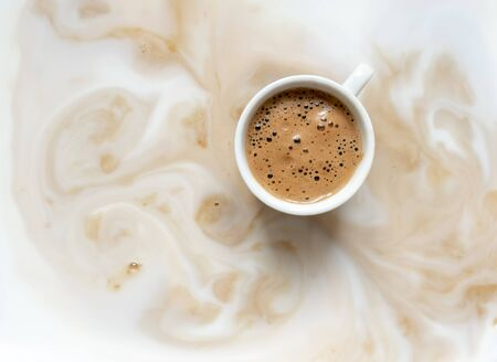 White cup of black coffee with foam on the white milk background. Cappuccino background with smoke and one cup, copy space.