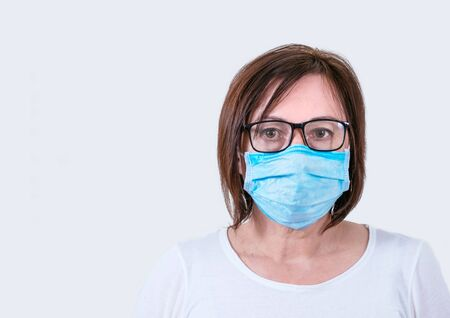 Portrait of a middle aged woman in medical mask. Sick woman average age in glasses on the white background.