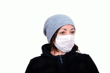 Portrait of a middle aged woman in white medical mask. Sick woman average age in jacket and cap on the white background.