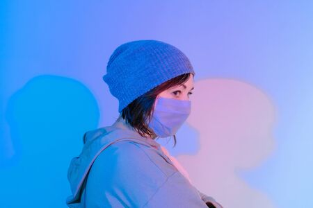 Middle aged woman in medical mask on the pink and blue background. Sick woman average age in cap on the stereet with neon lights.