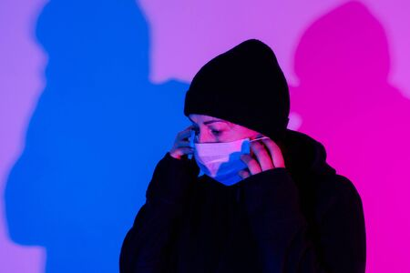 Woman in medical mask on the pink and blue background. Sick woman average age in cap on the stereet with neon lights.
