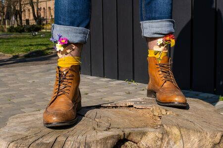 Men's pair of legs in the yellow shoes stands on the green grass. Yellow and pink spring flowers glues on the legs by adhesive tape.