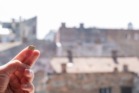 Hand holds a SIM Card on the street background with sky and houses, copy space. Stock fotó