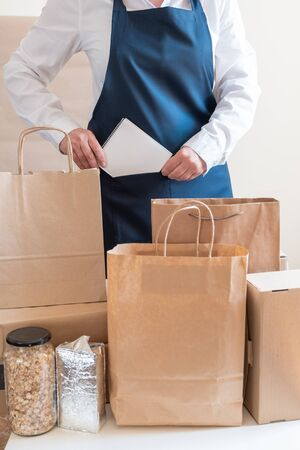 A lot of Craft Paper Bags and Boxes stay near by Packer. Worker of Delivery Service in Uniform Packing Order for Customer.