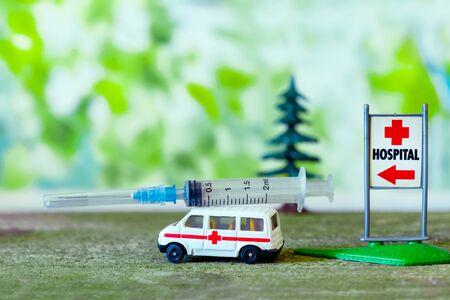 Toy ambulance car with syringe near sign Hospital on blue background.