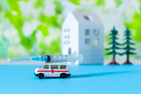 Toy ambulance car with syringe, white house and trees near sign Hospital, blue and green bright background. Stockfoto