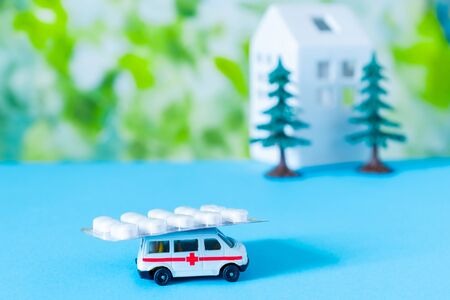 Toy ambulance car with medical pills, white house and trees on the blue and green bright background.