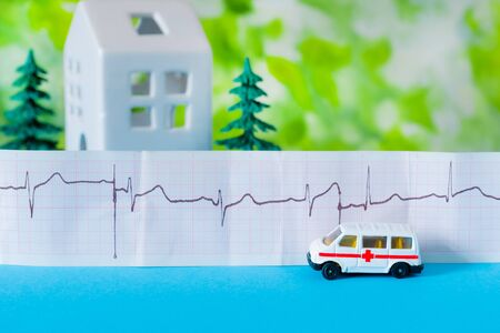 Toy ambulance car with sheet of cardiogram, white house and trees on the blue and green bright background. Stockfoto