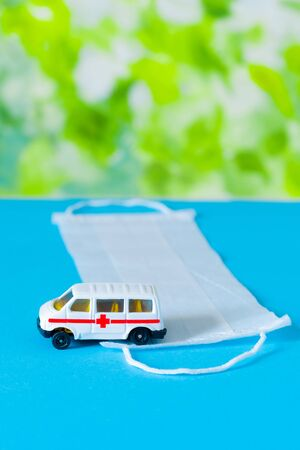 Toy ambulance car with white medical mask on the blue and green bright background.