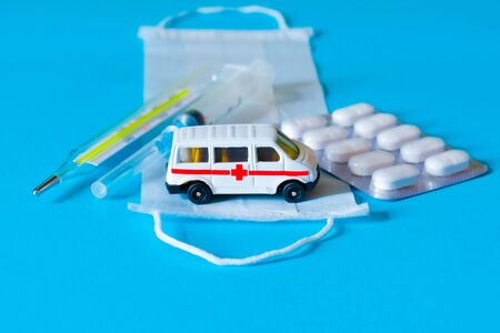 Toy ambulance car with white medical mask, pills, termometer and syringe on the blue background.