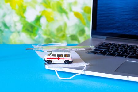 Toy ambulance car with white medical mask and laptop on the blue and green bright background.