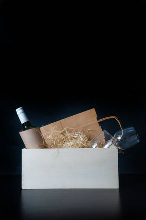 Wine Bottle and Glasses in white box with straw on the black background. Concept of Delivery Service for Customer. Stock fotó
