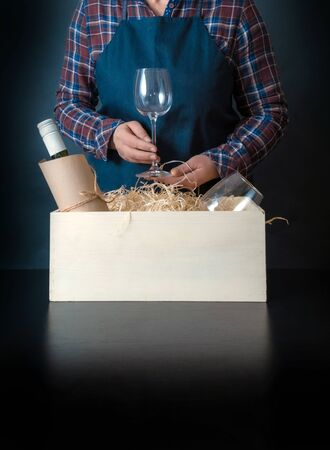 Female Worker of Delivery Service Packing a Wine Bottle and Glasses to box with straw for Customer.