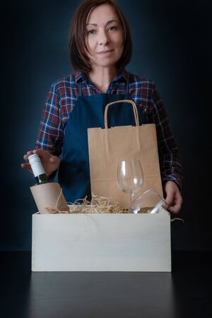 Female Worker of Delivery Service Packing Wine Bottle and Glasses to box with straw for Customer.
