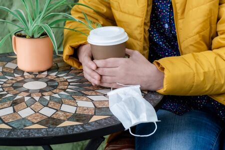 Female hands holding cup of coffee and medical face mask. Woman sitting outside in cafe, concept Coffee To Go.
