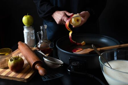 Chef's hands cut ripe apple for cooking apple dessert on the electric iron pan, black background.