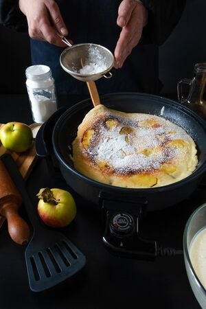 Traditional Dutch Pancakes with apples on the electric iron pan on the black background.