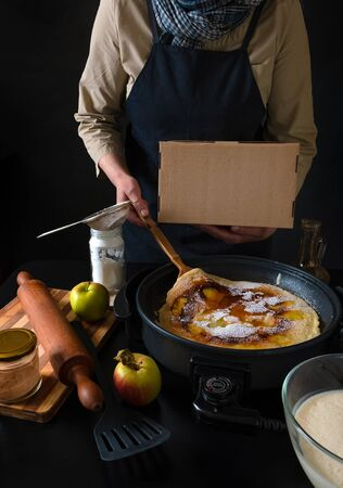 Chif cooking food take away, concept delivery service. Traditional Dutch Pancakes with Apples on the Electric iron Pan.