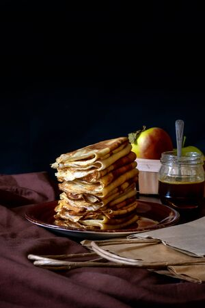 Traditional Pancakes with Apples and packaging carton bag on the black background. Concept delivery food service take away.