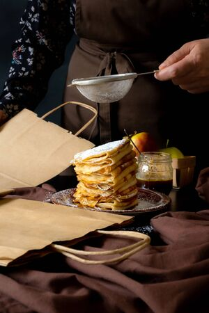 Chif cooking food take away, concept delivery service. Traditional Pancakes with Apples on the black background.