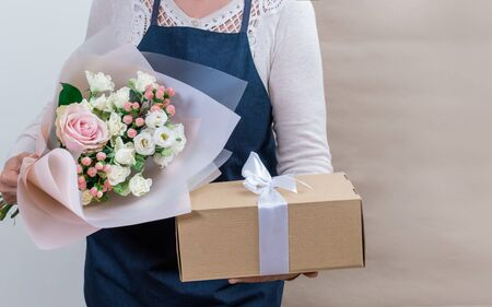 Female Worker of Delivery Service in Uniform Packing Flowers in paper bag and bag for Customer on the White and Craft Background. Stock Photo