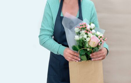 Female Worker of Delivery Service in Uniform Packing Flowers in paper bag for Customer on the White and Craft Background. Stock Photo