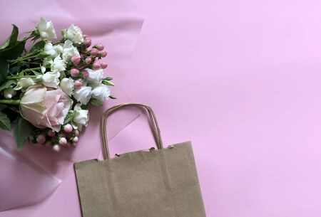 Pink Flowers and Craft Paper on the pink background. Concept of Delivery Service Packing Order for Customer.