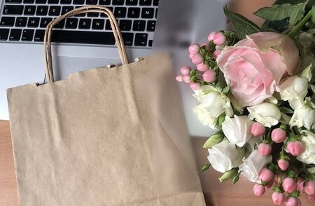 Pink Flowers and Craft Paper Bags on the Laptop. Concept of Delivery Service Packing Order for Customer. Stock Photo