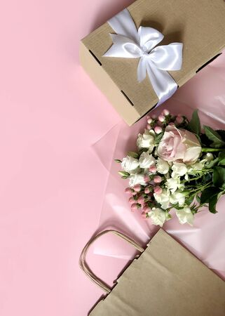 Pink Flowers, Craft Paper Bags and Boxes on the pink background. Concept of Delivery Service Packing Order for Customer.