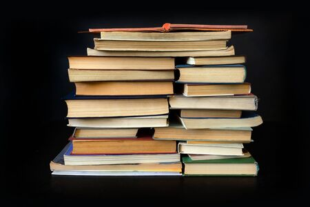 Stack of Old Books with Laptop on table on the Black Background. Zdjęcie Seryjne