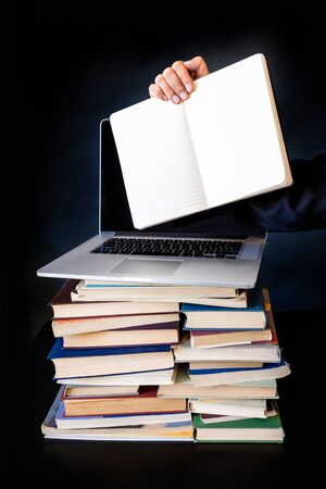 Stack of Old Books with the Laptop at the top. Hand Holding notebook on the Black Background in the Library.