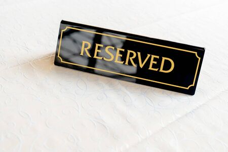 A tag of reservation placed on table. Reserved in a restaurant or summer terrace of cafe.