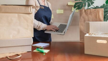 A lot of Craft Paper Bags and Boxes stay near by Packer with laptop. Worker of Delivery Service in Uniform Packing Order for Customer.