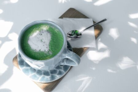 Cup of Green Matcha latte Coffee or Tea on white wooden background with sun light and shadow.